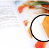Opengeslagen catalogus met uitvergrote uitsnede: garen (steken) licht zichtbaar